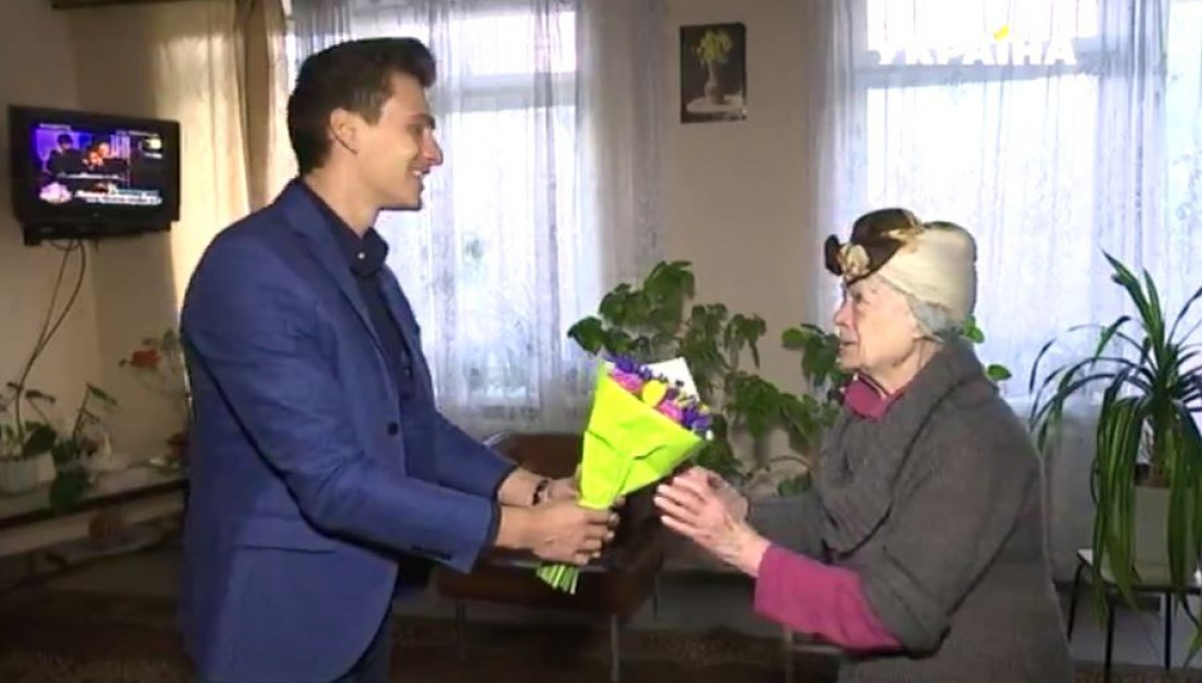 Александр Скичко вручает букетик пожилой женщине