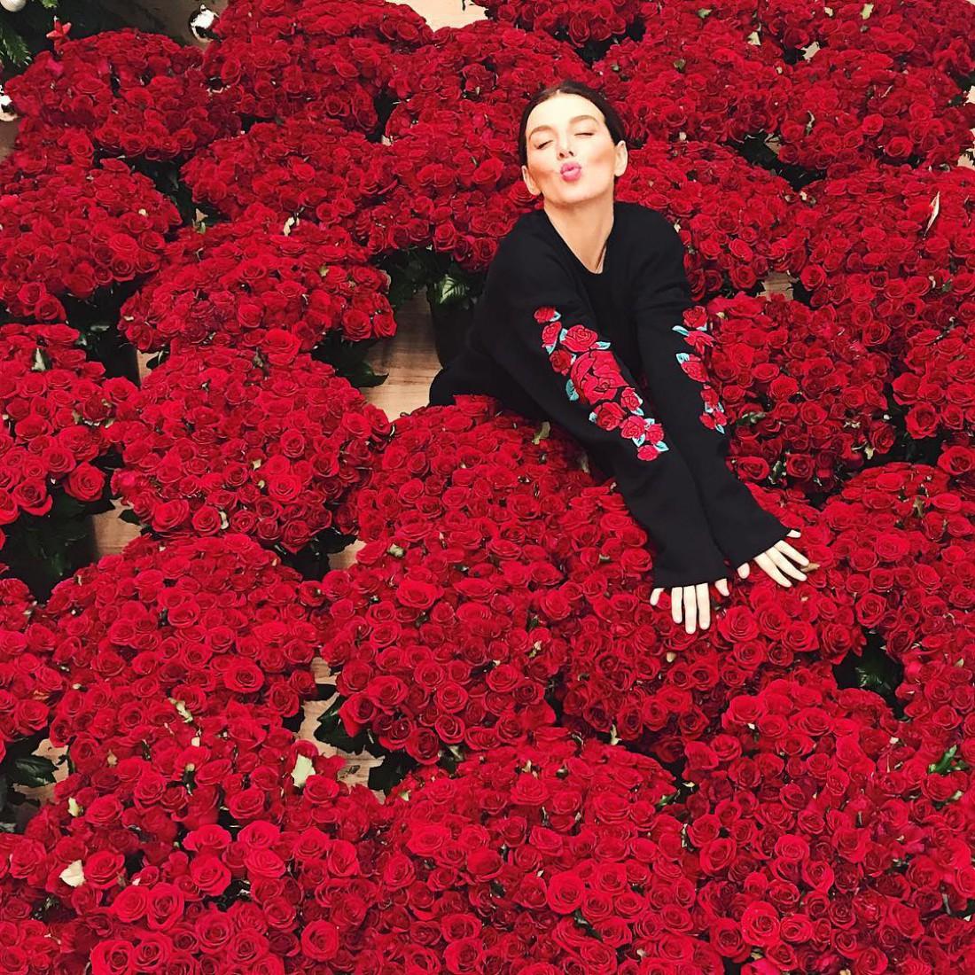 Анна Седокова сидит среди роз