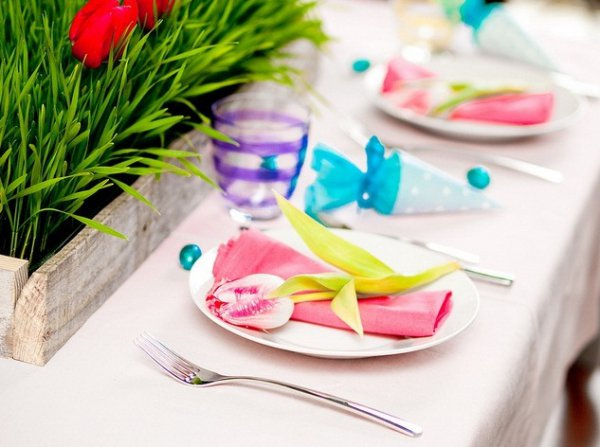 Сочная зелень в центре стола хорошо сочетается с яркими салфетками и маленькими тюльпанчиками на тарелках
