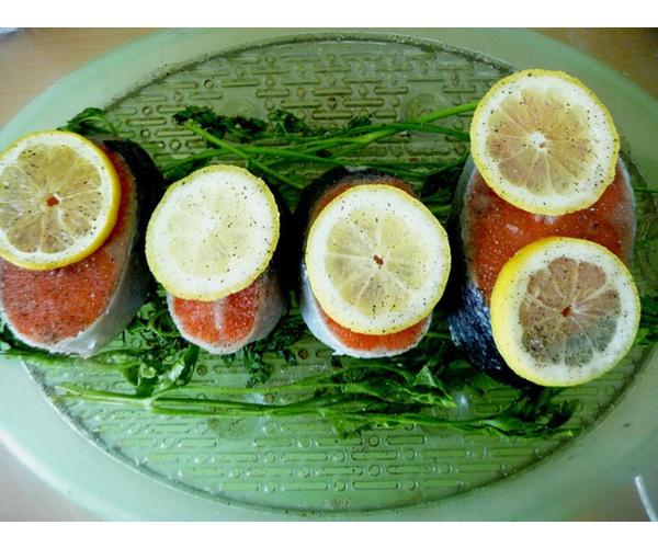 Рыбные стейки промыть, дно пароварки выложить зеленью петрушки, затем положить рыбу. Приправить по вкусу, добавить ломтки лимона.