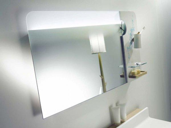 Большое зеркало с задней подсветкой оснащено несколькими небольшими открытыми полочками, стаканом для зубных щеток и стильными часами.