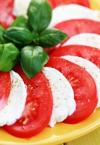 """Классический вариант подачи капрезе – """"веер"""" из помидоров и сыра, украшенный базиликом."""