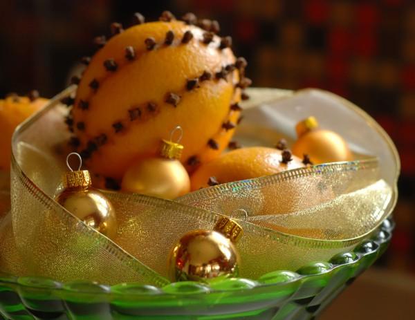 Эффектно смотрится прозрачная салатница, наполненная елочными игрушками и фруктами