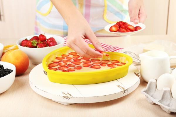 Выложить тесто в форму, разложить сверху кусочки клубники.