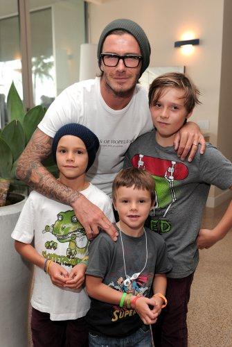 Дэвид Бекхэм с сыновьям. Самый младший, Круз, по центру