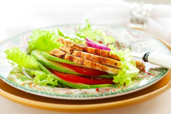 Сэндвич из листьев салата, авокадо, томатов, запеченного куриного филе и красного лука.
