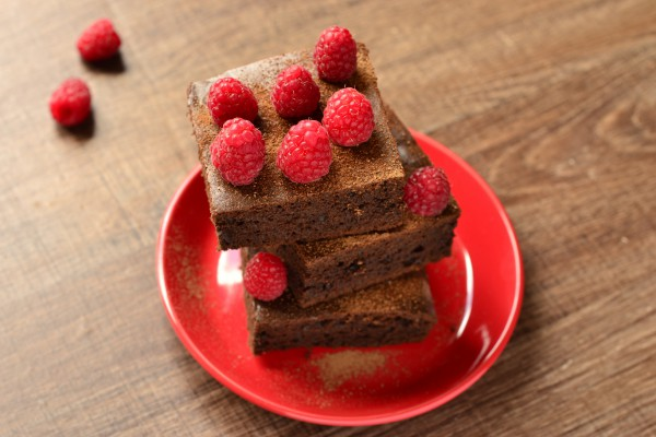 Брауни с бананами и малиной Ингредиенты: 200 г шоколада с 70% содержанием какао, 1 спелый банан, 1 чашка малины, 2 яйца (разделенных), 3 ст.л. темного какао без сахара, 1/4 чашки сахара, 1/4 чашки масла