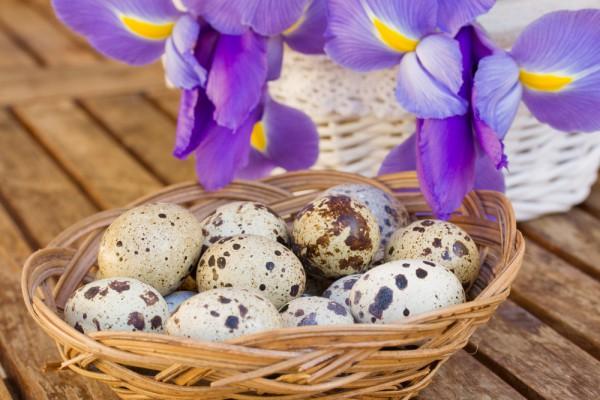 В центр стола можно поставить декоративную корзинку с перепелиными яйцами и букет ирисов.