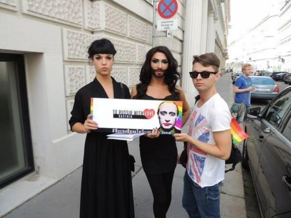 Кончита Вурст держит в руках табличку с изображением накрашенного Владимира Путина