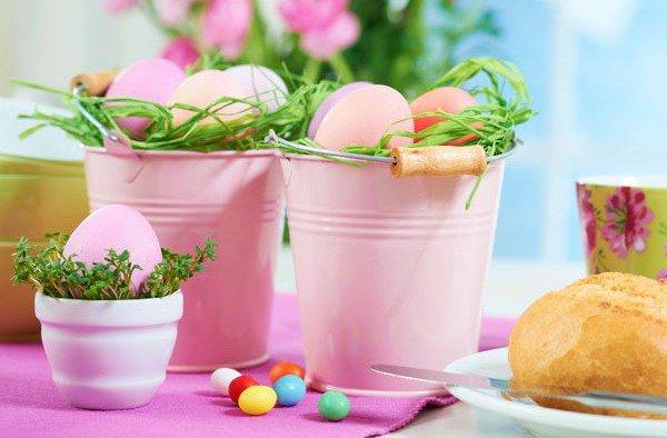 Пасхальная композиция: яйца, окрашенные в бледно-розовый цвет в декоративных ведерках, оттененные сочными красками свежей зелени