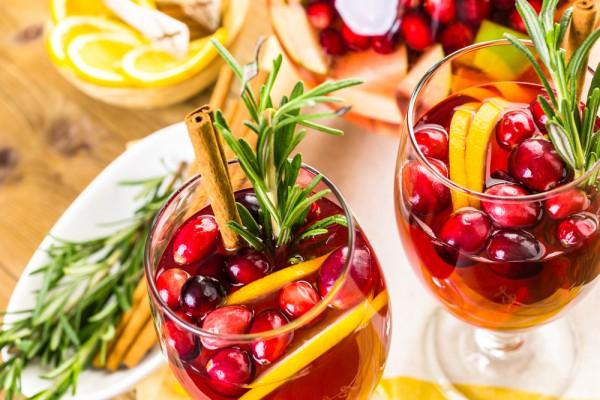 Сангрия из клюквы Ингредиенты:  2 чашки свежей или замороженной клюквы 1 стакан сахара 1 чашка воды 1 (750 мл) бутылка красного фруктового вина 1/2 чашки бренди 1 чашка свежевыжатого апельсинового сока свежая клюква, апельсин, яблоки, корица, розмарин лед