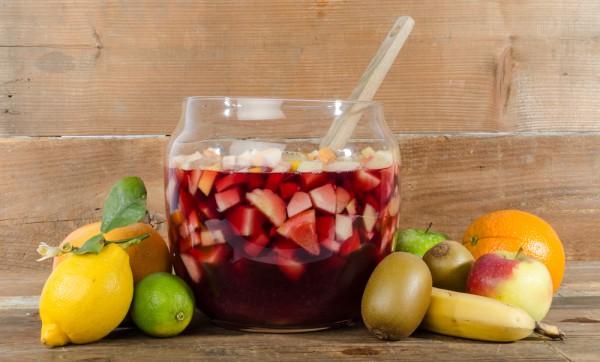 Фруктовая сангрия домашнего приготовления Ингредиенты:  ⅞ стакана сахара ¼ чашки воды (для сиропа) ½ чашки трипл сек ⅓ чашки бренди 2 яблока 1-2 киви 1-2 апельсина 1 банан 1 лайм или лимон 1,5 л красного вина лед