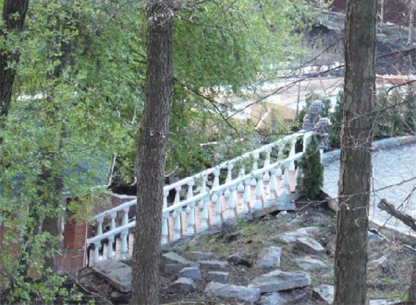 Дом вписан в склон, поэтому трудно определить его этажность – от двух до четырех этажей. Есть два небольших озера напротив дома. Лестницы к большой беседке на берегу озера украшены двумя львами.