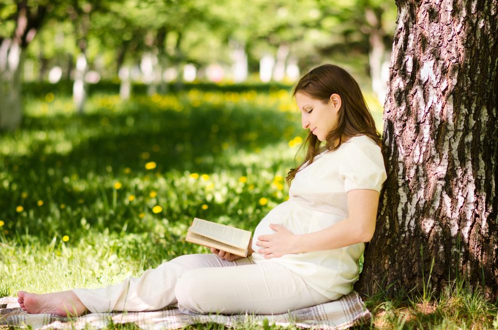 Беременная читает в парке