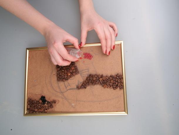 Дальше аккуратно приклеиваем зерна и бисер, постепенно заполняя всю поверхность картины.