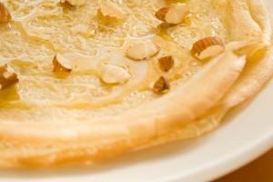 Готовые блинчики полить медом и посыпать орехами