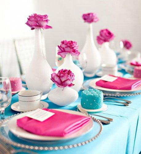 Ярко-розовые цветы хорошо сочетаются с белой посудой и голубой скатертью
