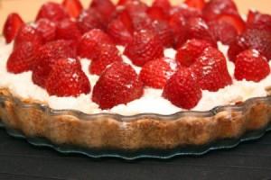 Готовый пирог украсить клубникой и посыпать сахарной пудрой
